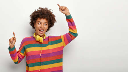 Energetic carefree African American female dances with raised arms, enjoys nice track, listens mucis via headset, wears casual loose striped colorful jumper, feels relaxed and glad, isolated on white
