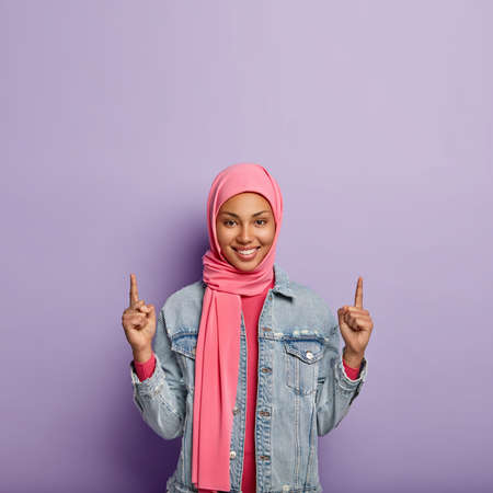 Islamic fashion concept. Glad positive female with specific appearance and clothes, points above on free space, shows something upwards, wears fashionabe jacket. Girl in hijab advertises object up
