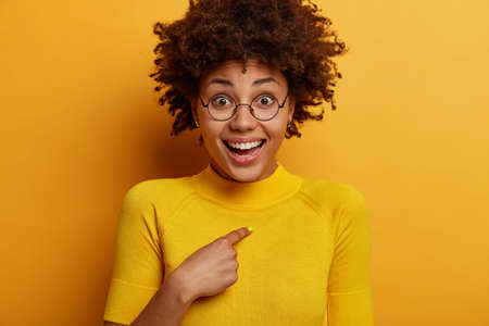Positive dark skinned Afro American woman points at herself, asks who me, happy to be chosen or to win, wears bright yellow clothes, poses indoor. Happy reaction, good emotions and feelings.