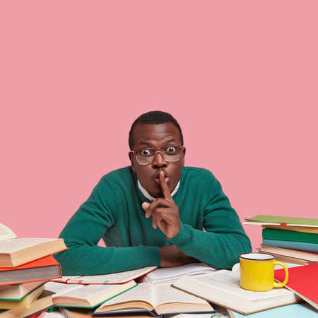 Photo of African American male bachelor keeps fore finger on lips, asks not making noise while studying, wears green sweater, drinks hot beverage, poses against pink wall with blank space above