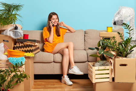 Happy female owner of new apartment, calls friend via cell phone, shares impressions about buying flat, gets ready to unpack boxes with household items, wears loose orange t shirt and sneakers