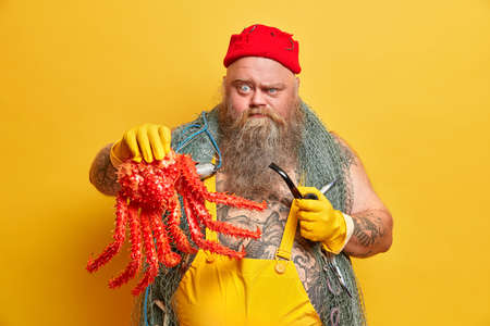 Horizontal shot of serious plump seafarer has good knowledge of sea rules, fishing skills, shows big red octopus, smokes pipe, ready to take orders from superiors, undergoes lifeboat operations Stock Photo