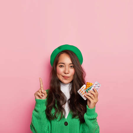 Photo of adorable woman points above, holds painkillers, has problems with health, shows way to chemists shop, dressed in green fashionable outfit, isolated on pink. People, disease, curing concept
