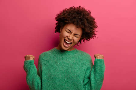 Ecstatic curly young woman exclaims and clenches fists with joy, feels like winner, triumphs and celebrates success, wears green sweater, poses against crimson background, celebrates victory