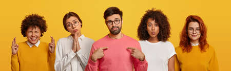 Unimpressed bearded man points at himself, four women stand near him, pray and beg for something, have glad expressions, wear spectacles, isolated over yellow background. Body language, emotions