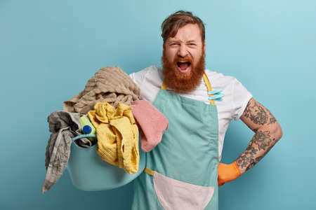 Photo of annoyed bearded man busy with housework, holds basket full of laundry and detergent, wears apron, shouts loudly, feels bothered, isolated on blue background, tired of doing washing.