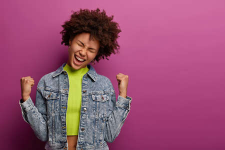 Relieved joyful Afro American woman makes fist pump, clenches fists and triumphs achieving goals, receives awesome news, wears denim jacket, becomes champion, isolated over purple background Banco de Imagens