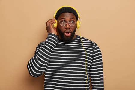 Indoor shot of emotional shocked bearded man listens modern music in headphones, looks with stupefied expression, surprised sound disappeared, wears black and white striped jumper, poses indoor