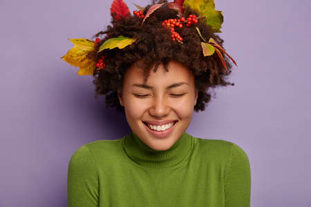 Close up portrait of lovely Afro American woman laughs out loudly, listens hilarious joke, has broad toothy smile, keeps eyes closed from pleasure, wears autumn leaves stuck in hair being in good mood