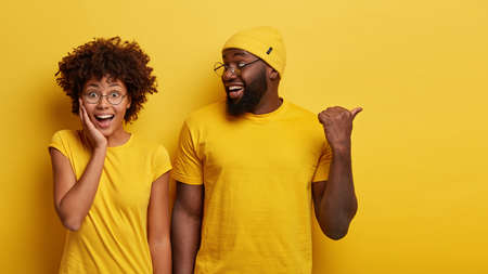 Studio shot of cheerful woman hears advice from boyfriend who tells something and points aside with thumb, dressed in similar yellow t shirts, being friendly team of coworkes. Lets go there