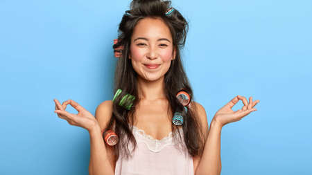 People, relaxation and morning time concept. Pleased young lovely woman with Asian appearance, keeps hands in peace gesture, dressed in nightwear, wears hair curlers for being curly. Body language