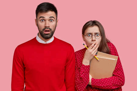 Horizontal shot of puzzled bearded man in red sweater, frightened girlfriend with pencil and spiral notepad, react on stunning news from professor, isolated over pink background. Classmates indoor Standard-Bild