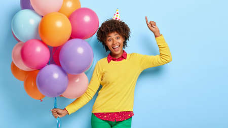 Attractive positive dark skinned woman carries multicolored birthday balloons, laughs and points upwards, wears cone hat, fashionable clothes, prepares for having holiday. Celebration and fun Banque d'images