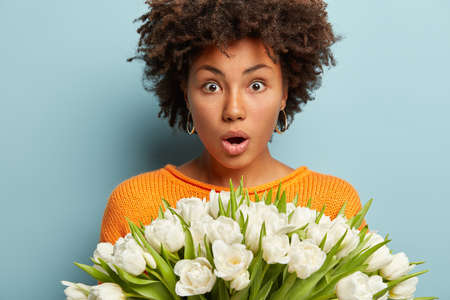 Gorgeous stupefied woman with curly hairstyle, opens mouth from surprisement to notice huge bouquet, carries white tulips, has dark skin, isolated over blue background. First spring flowers.