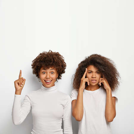 Happy Afro American woman points above fore finger, shows awesome product upwards, her intense friend touches temples, tries to recall important information, has bad memory, has bad headache