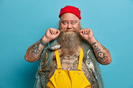 Glad fisherman curls mustache, has thick beard, carries fishing net on shoulders, spends free time for hobby and soul, wears red hat and overalls, has tattoed body, enjoys favourite activity