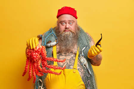 Image of bearded male mariner poses with octopus in hand, has good navy achievemnts, smokes pipe, dressed in yellow overalls, has traveling way of life, carries fishing net, works on board ship