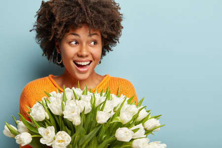 Wow, what wonderful flowers on Womens Day. Tender smiling African American woman with crisp hair, poses with white tulips, looks aside happily, isolated over blue studio wall, blank space for text