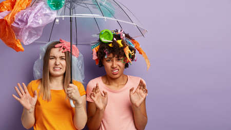 Two dissatisfied mixed race women look with aversion, see much garbage, express protest against pollution of nature, carry umbrella made of polythene, isolated over purple wall with free space