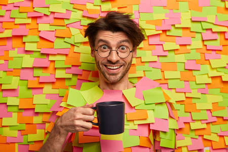 Photo of handsome cheerful businessman in eyeglasses holds cup of coffee, smiles happily, has break after work, has pleasant talk while sips hot beverage, sticks head through colorful stickers