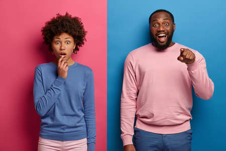 Speechless Afro American woman gasps from fear, happy bearded man points directly at camera, express shock and happiness, dressed in casual bright clothes, pose against two colored background