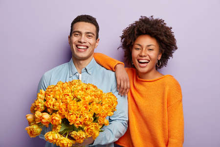 Happy diverse couple have date. Cheerful handsome Caucasian guy holds huge bunch of orange tulips, gives flowers to dark skinned girlfriend, congratulates with birthday. Relationship concept