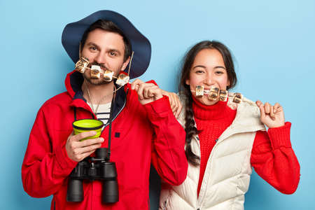 Photo of female and male tourists eat tasty marshmallow roasted on bonfire, spend pastime in nature, like traveling and having adventures, wear casual clothes. Two friends have pinic in forest