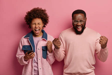 Emotional curly Afro American woman and bearded man shouts loudly, keep fists clenched, have mouthes opened, celebrate or support something, wear casual outfits, isolated on pink background.