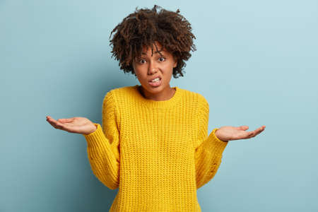 Portrait of unawre unsure dark skinned woman spreads palms in bewilderment, being questioned what to present for parents on holiday, has puzzled facial expression, models over blue background