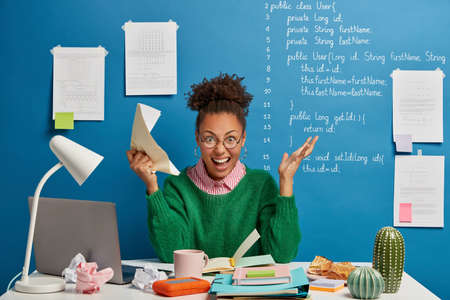 Mad female entrepreneur gets crazy because of much work, screams angrily, holds crumpled paper, stressed of havig deadline, has problem with computer, poses at workplace, stuck with hard task 免版税图像