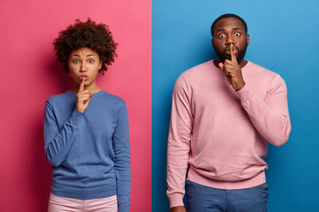 Photo of surprised Afro American woman and man press index fingers on lips, asks be silent and mute, tells secret to someone, not spread rumors, dressed in colorful sweaters. Pink and blue wall
