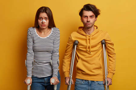 Unhappy couple got into accident, suffer from painful feelings and various traumas, stand next to each other on crutches, isolated on yellow background. Accident insurance and medical concept