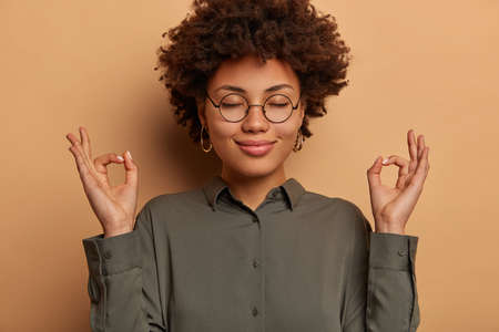 Businesswoman has meditation break to release negativity and bad emotions, stands with closed eyes, stands in lotus pose, makes mudra gesture, wears formal grey shirt and spectacles, poses indoor