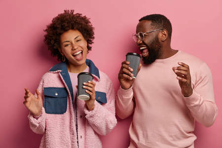 Horizontal shot of amused cheerful woman and man with dark skin have fun during coffee break, sing song along, dance carefree, wear casual pastel clothes, poses over pink wall. Happy emotions
