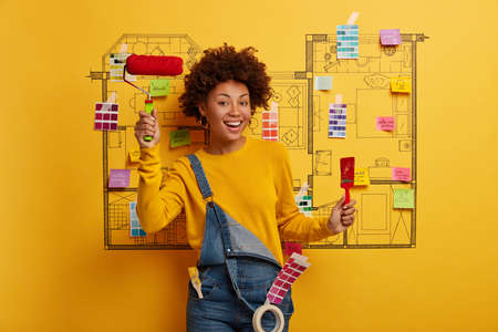 Renovation at home. Positive African American woman holds paint brush and roller, busy with painting, thinks about house improvement, dressed in jean overalls, creative sketch on yellow wall
