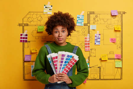 Woman decorator with Afro hairstyle holds color palette, makes decision about necessary tone for house decorating, examines samples, stands against drawn building sketch, going to paint walls