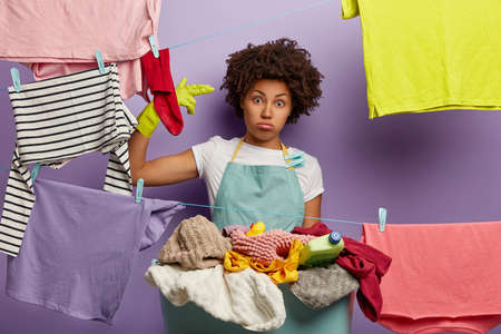 Tired housewife busy with laundry at home, shoots in temple with two fingers, wears rubber protective gloves and apron, stands near clotheslines with hanged clean clothes, has tiresome weekend