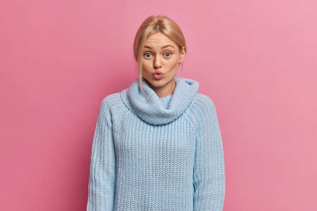 Lovely young woman with no makeup blonde combed hair and blue eyes pouts lips and looks surprisingly at camera wears casual blue sweater with collar wants to kiss someone isolated on pink wall Фото со стока
