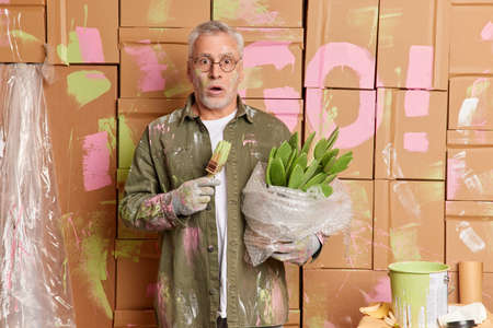 Shocked aged man decorator wears dirty clothing stares bugged eyes busy painting walls in new apartment holds cactus improves house. Repair and building concept. Home decorating. Do it yourself.
