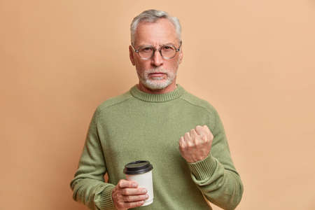 Strict angry bearded senior man looks seriously at camera tries to warn you holds disposable cup of coffee wears casual jumper poses against brown background. I will show you. Negative emotions