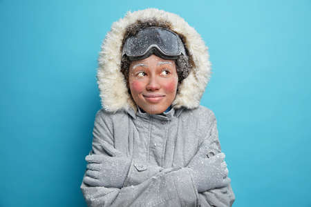 Frozen woman embraces herself trembles from cold covered with hoarfrost looks gladfully wears snowboard goggles winter jacket and gloves smiles pleasantly isolated over blue studio background