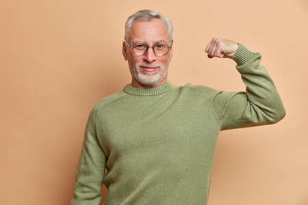 Confident satisfied grey haired man raises arm and shows muscle demonstrates results after regular training in gym wears spectacles and jumper isolated over brown background being proud of himself 版權商用圖片