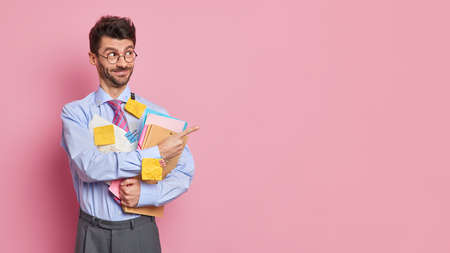 Creative unshaven office worker in eyeglasses and formal wear holds folder and papers wears sticky notes on shirt points away on blank space isolated over pink background gives ideas for project