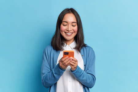 Smiling charming brunette Asian woman uses mobile phone happy texting in social networks addicted to modern technologies wears casual jumper isolated over blue background. Online communication