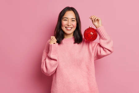 Photo of pretty brunette Asain woman happy to celebrate winter holidays shows best offer for your Christmas tree holds big red ball to decorate prepares for New Year wears casual pink jumper