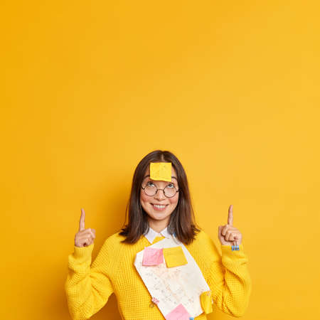 Positive successful female manager in casual sweater with papers and stickers stuck by paperclips smiles and points on copy space against yellow background demonstrates something for office. Stock Photo