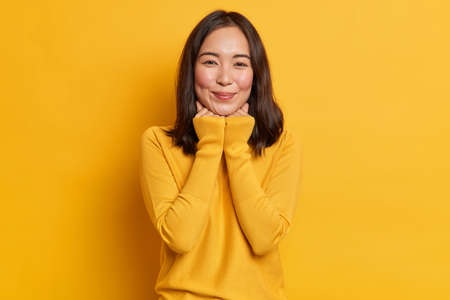 Studio shot of pretty young Asian woman keeps hands under chin has satisfied expression wears casual clothes isolated over yellow vivid background. Monochrome shot. Smiling eastern female model