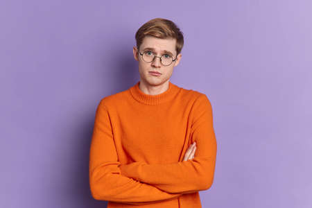 Displeased handsome young man has pity expression looks dissatisfied at camera keeps arms folded wears round spectacles and orange jumper isolated over purple background. Face expressions concept Banque d'images