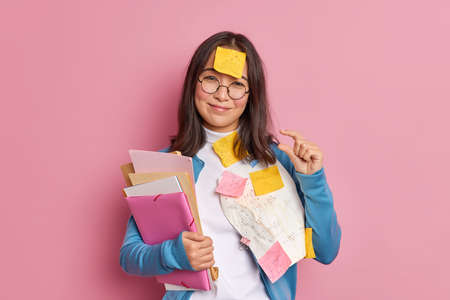 Glad brunette schoolgirl makes tiny gesture tells she needs little more time for exam preparation has sticky note stuck on forehead has deadline to finish project work isolated over pink background