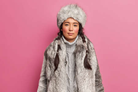 Portrait of arctic woaman with two pigtails dresses for cold climate wears grey fur coat and hat isolated over pink background. People winter season and clothes concept. Scandinavian female indoor